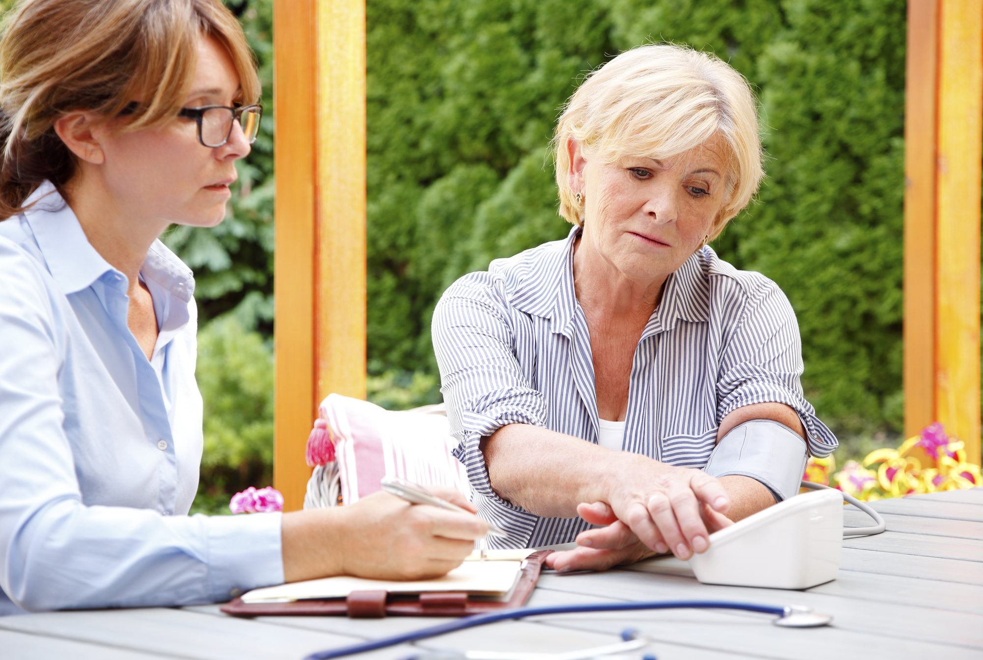 Elderly woman sitting in the garden with home health care nurse an using blood pressure.
