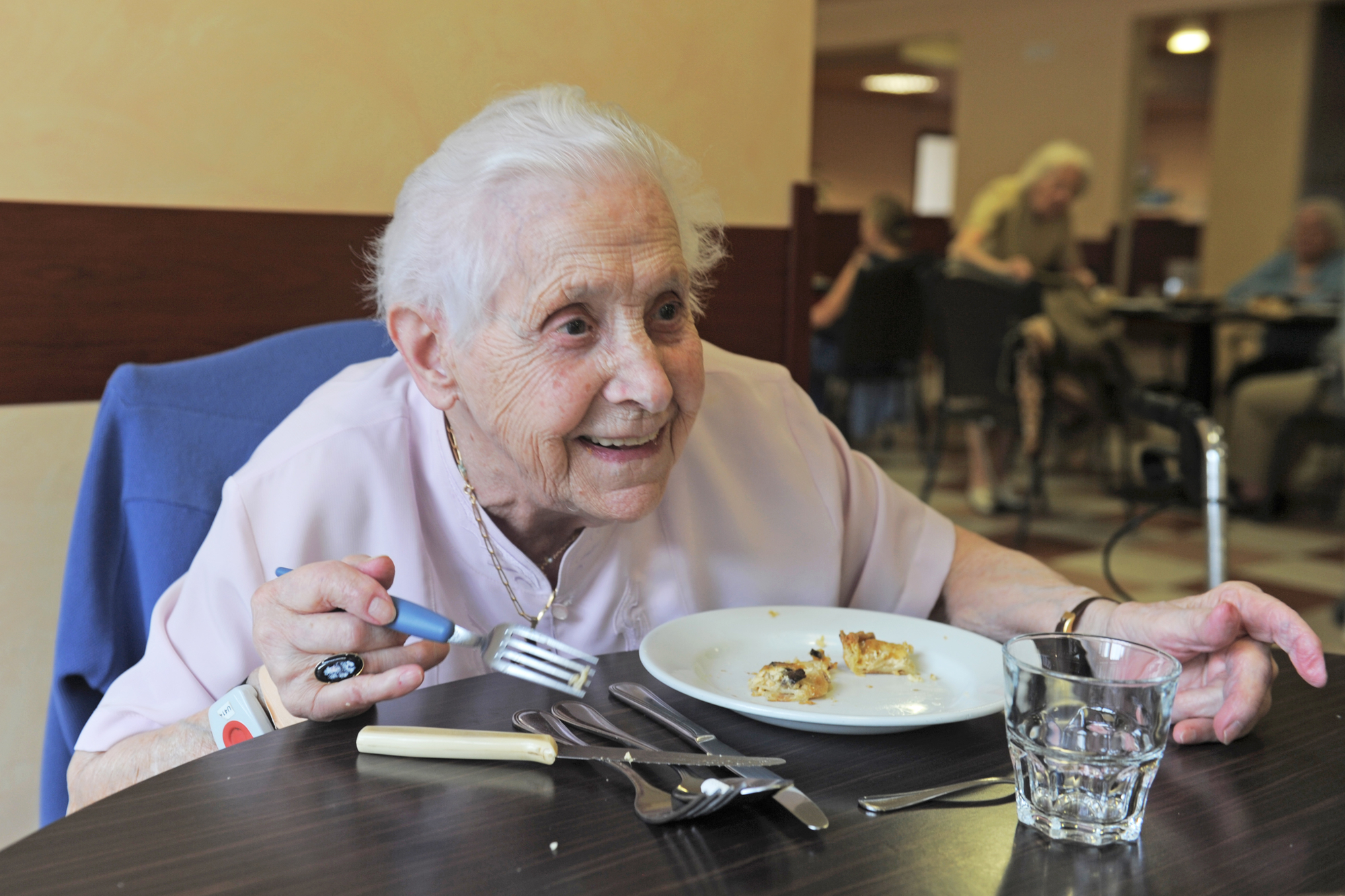 senior woman smiling and eating in a  retirement facility